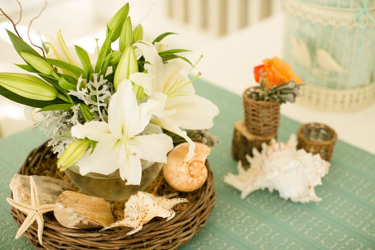 Casablanca Lily along with shells, foliage and drift woods adorning the registration table