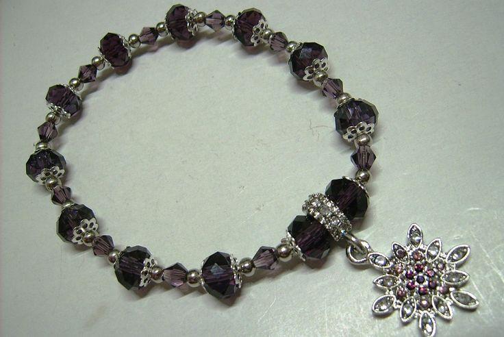 K-600. Padlizsán lila színű, csiszolt üveg gyöngyös, és lila kő medálos, gumis karkötő. 750.-Ft.