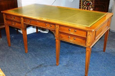 A cherry finish desk, rectangular top with skiver over kneehole drawer flanked by two short drawers, on square tapering legs, with pierced brackets..