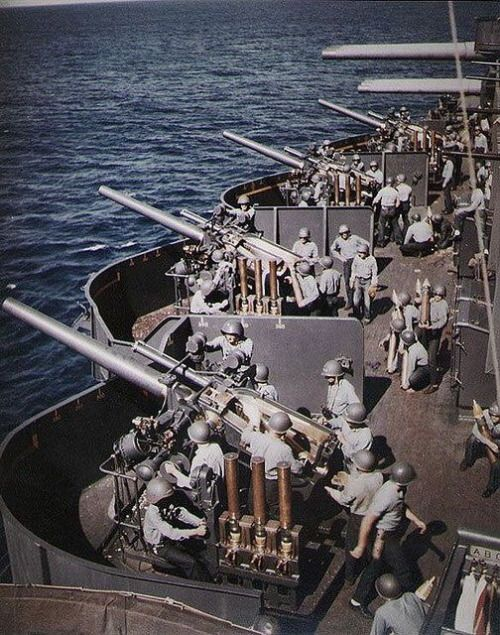 "The 5""/25 (127 mm) battery aboard the U.S. Navy battleship USS New Mexico (BB-40) prepares to fire during the bombardment of Saipan, 15 June 1944. Note the time-fuze setters on the left side of each gun mount, each holding three ""fixed"" rounds of ammunition; the barrels of 20 mm machine guns at the extreme right; and triple the 14""/50 (34.5 cm) guns in the background."