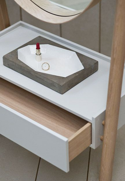 A full-length pivoting elliptical mirror with a shaker-style joint and brass rivet detail at one side held in an A-frame with a lacquered drawer box below.