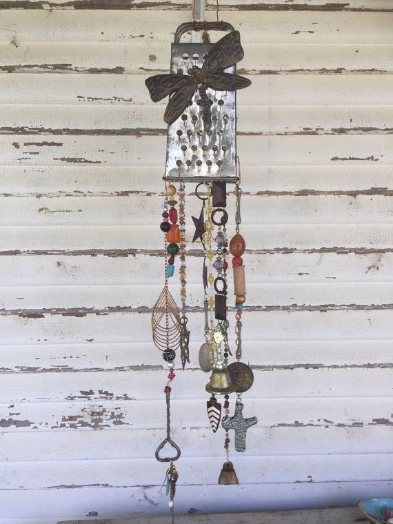 This vintage cheese grater has been brought to life as a unique piece of garden art. Hanging like a windchime, though not full of noise, it can grace any back porch and give you that eclectic flair youve desired. I use you all recycled items. The only thing I buy new is the wire so that itll last you. From the top where it hangs do the longest strand if is 34 inches long and 4 inches wide. Let me know if you have any questions. I make all of my items in a smoke and pet free environment.