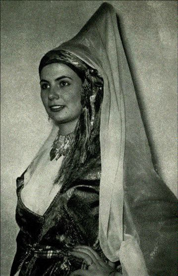 This is a historically authentic traditional Lebanese dress with the famous Middle Eastern  Tantour headdress which was extremely en vogue in the 18th and the 19th centuries in Lebanon.  This gown is a part of the wardrobe of the Lebanese high society and nobility. It is characterized by an ankle length Ghambaz made out of silk brocade with  delicate silver threads. The  full-length underpants are pure silk and stylized as Turkish pantaloons.