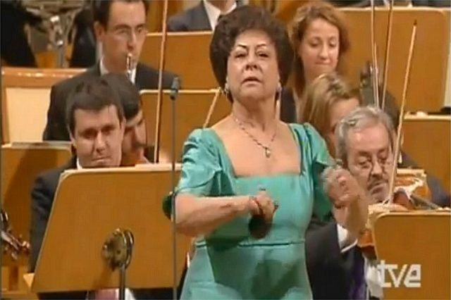 The orchestra plays a classical piece, but when she joins them, all becomes like magic