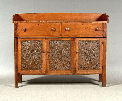 """Russell County, Virginia, pie safe, dovetailed and scalloped back panel above two broadly dovetailed drawers, front and sides with circular and star punched tins, side tins marked """"Aug 7 1859"""" [backwards], frame-and-panel back with two chamfered panels, cherry and poplar with figured mahogany veneer panels flanking two drawers, 51 x 63 x 21 in. Old refinishing, top with old stains, dents and separations from normal wear, lacking several pieces molding, several tins loose. Exhibited 1996…"""