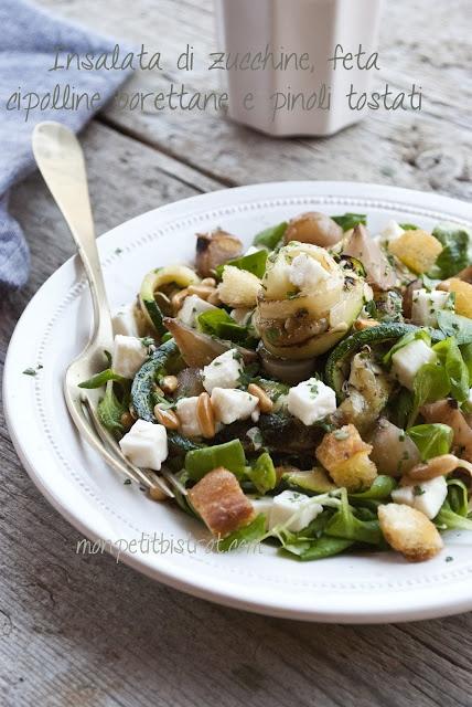 Insalata di zucchine, feta, cipolline borettane, pinoli tostati, su un letto di valerianella e crostini di pane tostati.
