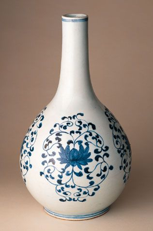 Bottle, Choson period (1392-1910),ca. mid- to late- 18th century.This long-necked bottle is marked by sharp precision and symmetry. On the globular body, repeating painted patterns of a lotus blossom encircled in scrolling leaves. #KoreanCeramics