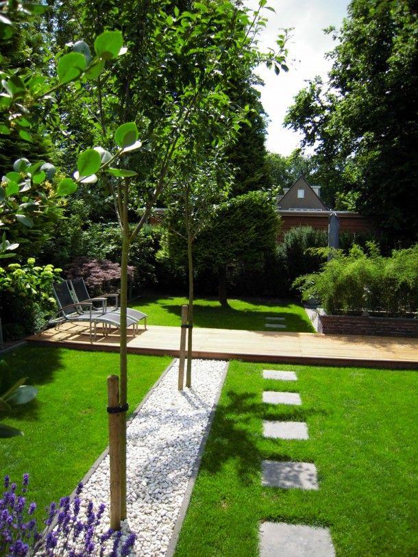 Groene achtertuin met kiezels en veel gras om op je rug te liggen en naar de lucht te kijken..