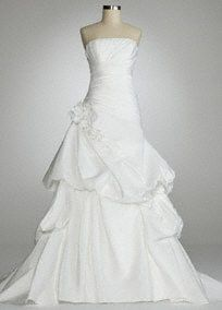 Make a dramatic entrance on your wedding day in this gorgeous strapless ballgown.   Strapless pleated bodice with a side draped pick up skirt and 3D rosette at the hip add just the perfect amount of detail.   Lace up back.  Chapel train.  Available in Soft White. Sizes 2-16.  Fully lined. Imported polyester. Dry clean only.