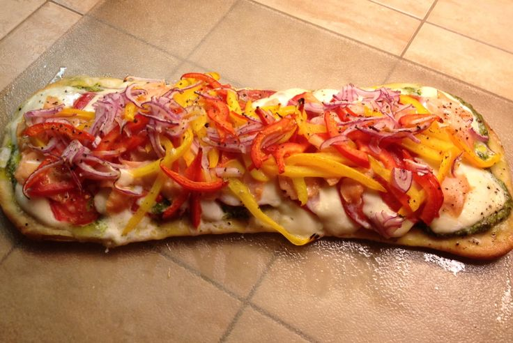 Flatbread pizza, made with homemade pesto, mozzarella, ripe tomatoes, golden beets, smoked salmon, red and orange peppers, red onion, mozzarella.