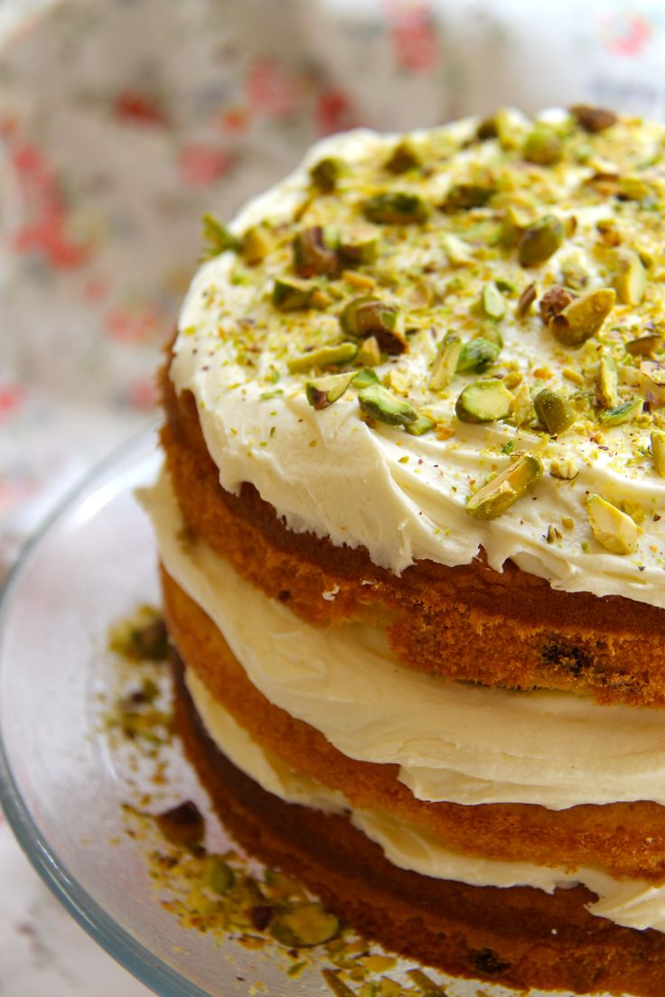White chocolate & Pistachio cake with white chocolate buttercream - deliciously light sponges full of white chocolate chips and pistachios, layered between thick servings of white chocolate buttercream!