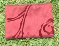 """This beautifully made recycled fabric zip bag is made by refugee women from Coffs Harbour, NSW TAFE.  Perfect for many uses. An ideal wallet, coin purse, make up bag, pencil case. You decide.  Made from recycled maroon printed curtain remnants, fully lined with recycled white material and sporting a recycled maroon zip too. This piece is funky and functional. The print is velour spiral on slightly shiny material.Bit of luxury!.  Measuring 6""""wide x 4.5""""high $12.95"""