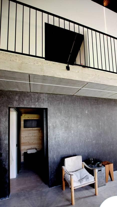 Käsityönä tehtyjen kaiteiden esikuvana ovat teollisuustilojen kaiteet. Betonilattia jatkuu myös kylpyosaston puolelle. Yhtenäiset materiaalit koko talossa lisäävät tilan tuntua.