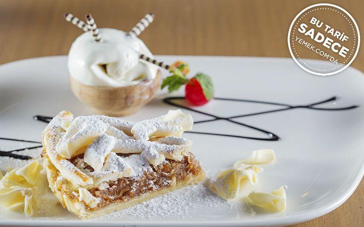 Apple pie tarifinde rendelenmiş elma, kuru kayısı parçaları, ceviz içi ve kuru üzümle hazırlanan iç harç; tereyağlı tart hamurunun iç kısmında pişiyor.