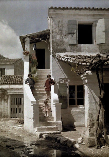 Girls stand on a stairway of a house in a Greek fishing village, Benizze, Corfu