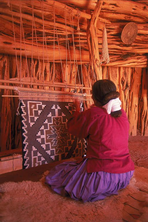 Navajo woman weaving a rug in her hogan