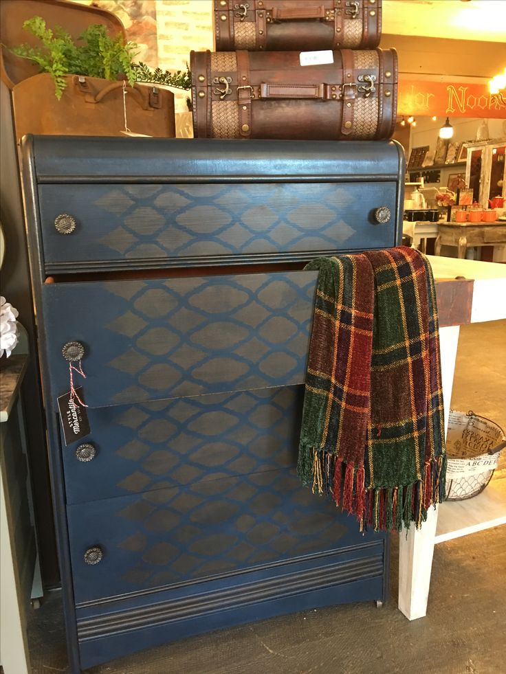 Dark blue with metallic stencilled detail on the drawer fronts make a simple vintage dresser a  stand out