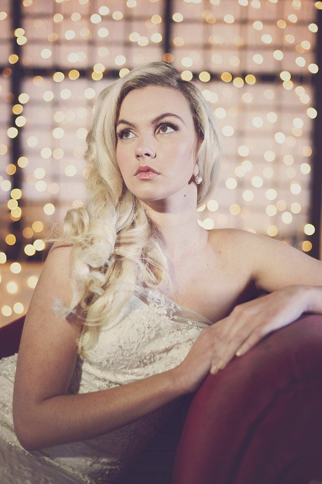 For this shoot, we wanted to portray the glamour of Old Hollywood. We used a simple backdrop of simple warm fairy lights and a dramatic red chaise lounge – and not much else! Our model's hair was styled in a voluminous, curled, va-va-voom down-style – reminiscent of the blonde bombshells of yesteryear. Make-up was kept natural and fresh, so as not to detract from the gorgeous gown.