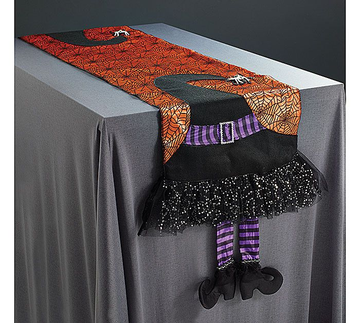 """Orange table runner with black spider web overlay. Has witch hat and dangling legs at each end. 13 1/2""""W X 62""""D Legs are 8 1/2""""Long"""