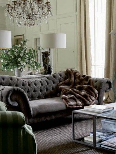 Luxuriate in the Living Room A tufted grey chesterfield, crystal chandelier, and fur throw