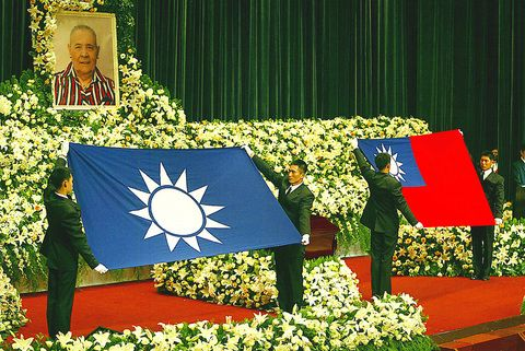 Funeral aides prepare to drape the Chinese Nationalist Party (KMT) flag and the national flag over the coffin of former first lady Faina Chiang Fang-liang at Taipei Veterans General Hospital yesterday.