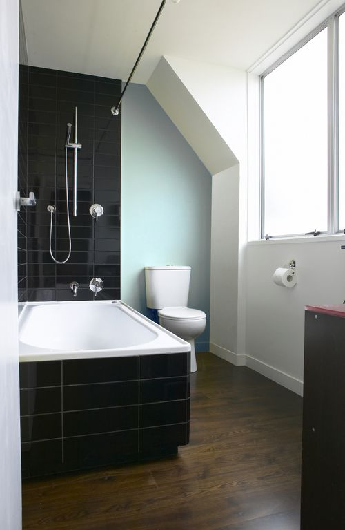Contemporary bathroom with black gloss tiles and dark oak timber flooring.