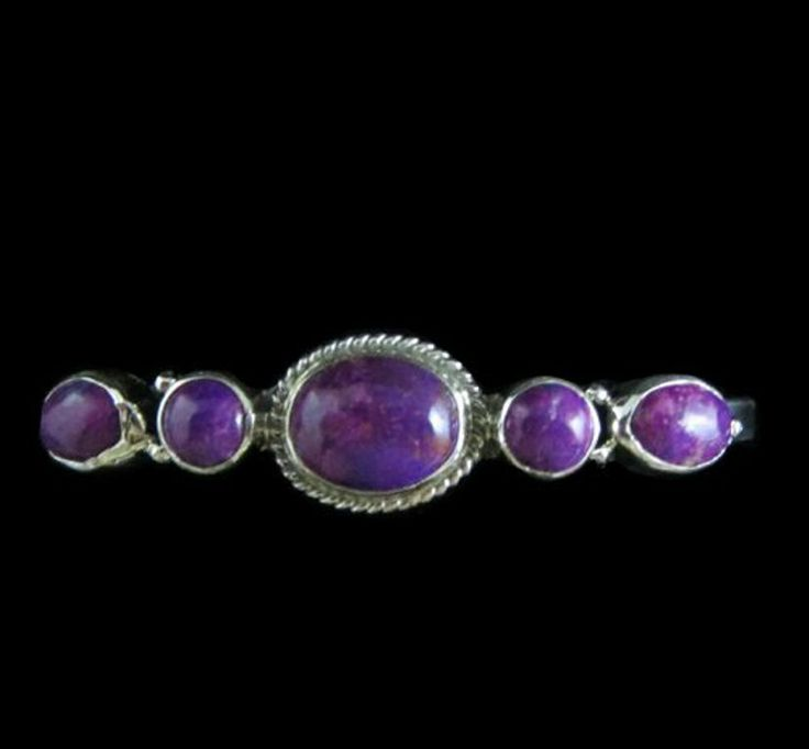 Cuff style bracelet with 3 oval and 2 round Magenta Turquoise cabochons http://nativeamericanstuff.net/magenta_turquoise_jewelry.htm