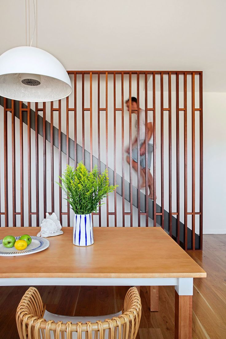 """Kristen and Gerard's bright coastal home:Gerard heads upstairs to the parents' retreat. The slatted joinery divider that masks off the stairs and adds interest to the dining area is made from jarrah. The vase and bowl are both from [Empire](http://www.worldofempire.com/