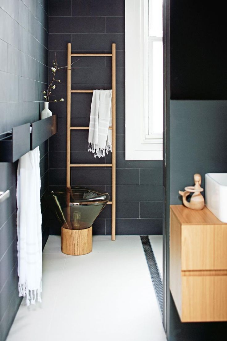 A lovely dark grey bathroom is warmed up with some wooden details