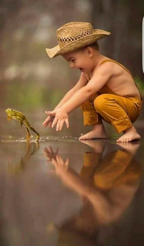 Cute little boy trying to catch a leaping frog!