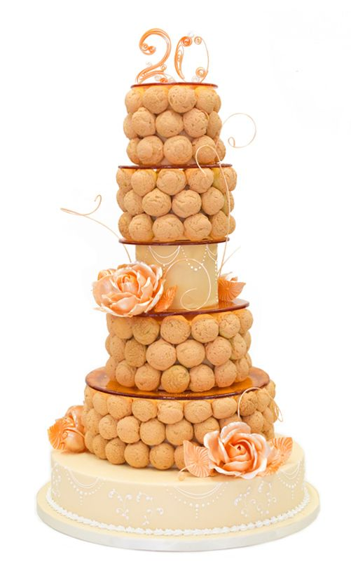 Twist on a traditional croquembouche: cream puffs topped with a sweet dough cookie, attached to tiers of cake and adorned with pulled sugar flowers and gum paste numbers from Sunny Lee and Nicole Bujewski, chef instructors at The French Pastry School