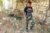 Regardez l'actualité - Libération Soldat de l'armée libre syrienne marchant près du cadavre d'un soldat des forces loyalistes