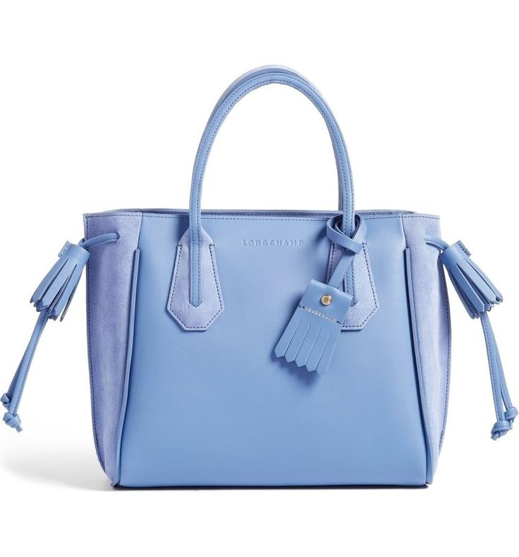 This modern bag features a compact sihouette in soft periwinkle blue, sleek rolled top handles, and detailed tassles
