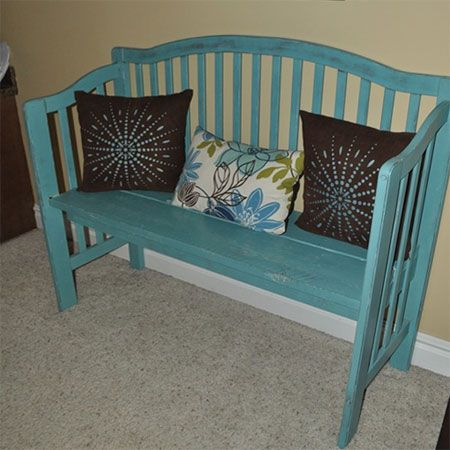 Turn an old crib into a bench by changing the paint color & adding throw pillows.