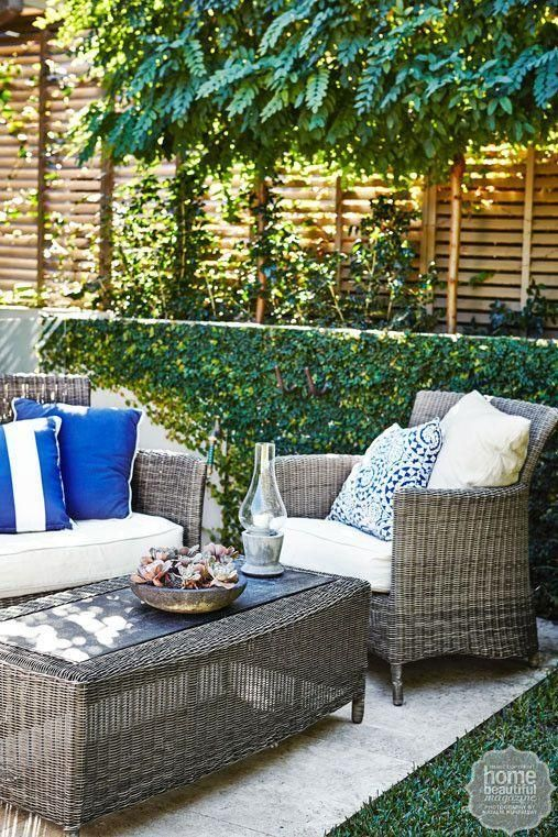 Outdoor inspiration: a low retaining wall overgrown with creeping fig creates a lush background for the outdoor rattan setting.