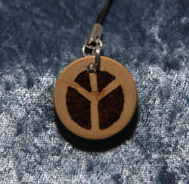 "Let your love for Peace dangle from your cell phone, wine glass, or whatever, and when people ask why the peace sign is 'upside down', you will have a chance to explain how this new version of the peace sign is a much more positive symbol.This small wooden charm has been burned by hand onto a wooden disc, approximately 1"" across. On the reverse side are the words Turn Peace Around. The disc is attached to a standard black cord cell phone lanyard using a miniature split ring.~~ Why is this…"