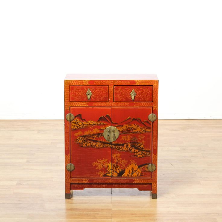 This asian bar cabinet is featured in a solid wood with a glossy vibrant red lacquered finish and shiny brass hardware. This chest has a large interior cabinet, 2 drawers and gold painted mountain range scenes, floral accents and birds. Eye catching storage piece perfect as a small buffet! #asian #storage #cabinet #sandiegovintage #vintagefurniture