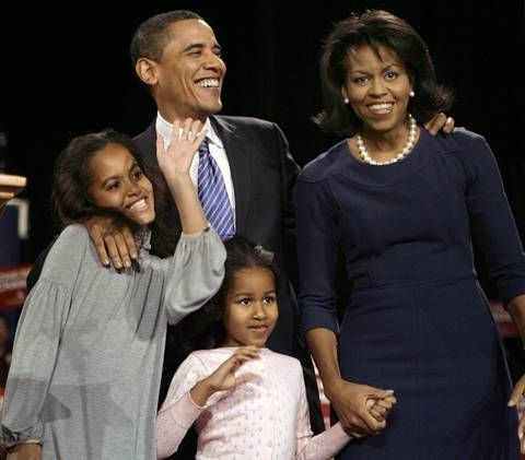 Barack Obama and his family greet supporters at an after-caucus rally in Des Moines, Iowa, after winning the Iowa democratic presidential caucus on Jan. 3, 2008. His wife Michelle wears a navy blue sheath with three-quarter sleeves.