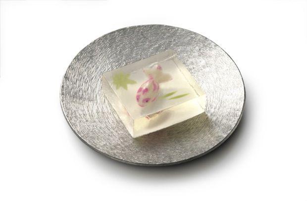 今日のおやつは、京都発祥、室町時代後期の創業以来、約480年の歴史を持つ和菓子屋「とらや」が作る季節の生菓子。どれも、眺めているだけで涼しくなりそうなお菓子ばかりです。上の生菓子は、水面に浮かぶ青葉の蔭を金魚が泳ぐ「若葉蔭」。寒天を溶かし、白双糖を加え煮詰めて水飴を加えた「琥珀製」のお菓子。夏の季語である金魚の姿が涼やかです。- colocal | 目にも涼しげ!金魚が泳ぐ「若葉蔭」ほか、和菓子の老舗「とらや」が生み出す夏の生菓子