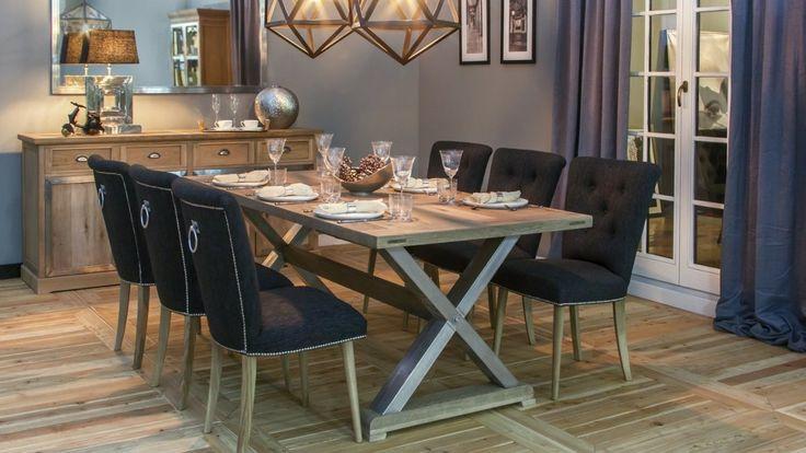 Komplet jadalniany na 6 osób: prostokątny stół z jasnego drewna z nogami w kształcie litery X oraz tapicerowane krzesła z  ćwiekami i ozdobnym uchwytem na oparciu. Eleganckie meble do jadalni.