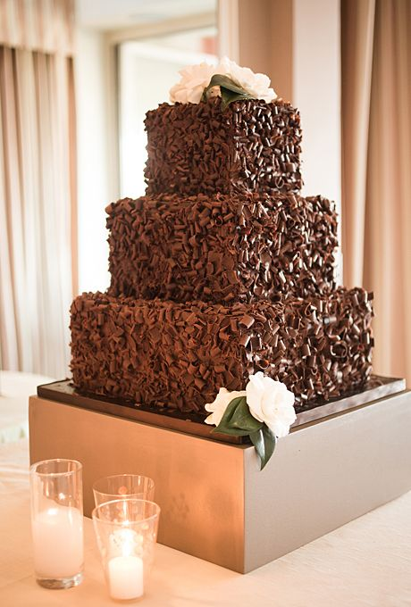 Brides.com: 22 Wedding Cakes for Dark, Modern Color Palettes. A Three-Tier Wedding Cake Covered in Chocolate Shavings. Los Angeles-based The Butter End Cakery whipped up Kaley Cuoco's show-stopping, upside-down wedding cake—it hung from a chandelier!—as well as this chocolate shaving-covered, three-tiered wedding cake. It looks like a giant chocolate truffle, and that's just the way we like it.  See more square wedding cakes.