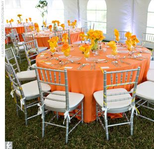 The tables were covered in orange linens with yellow napkins or yellow linens with orange napkins. At each place setting, a single rose in the contrasting hue was wrapped in each napkin.