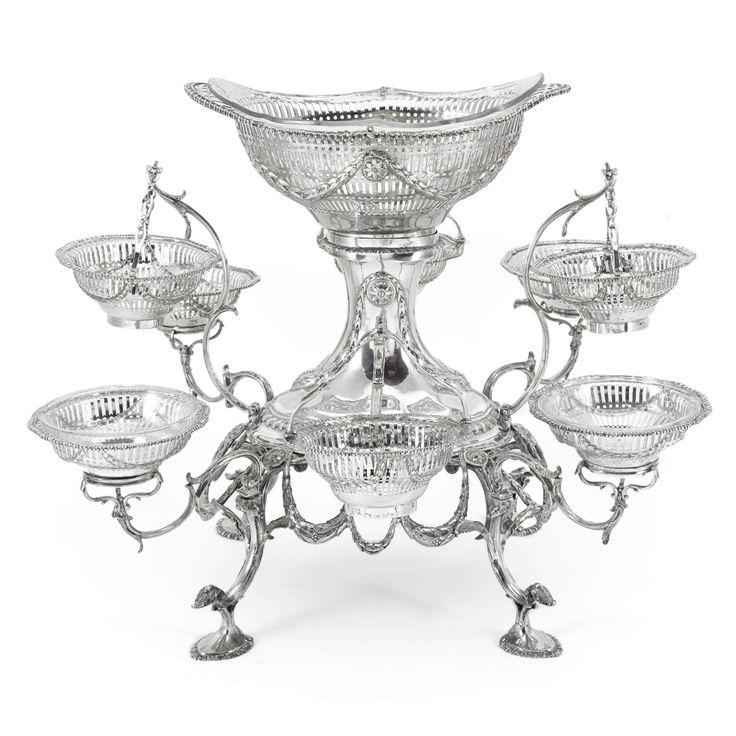 A George III silver epergne, Emick Romer, London, 1773 the central stand with laurel leaf festooning and gadrooned rims, eight detachable curving branches supporting similarly decorated sweetmeat baskets, four with swing handles, large central boat shaped basket, all engraved with a crest, later glass liners for central basket and two sweet meat basket