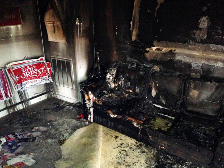 """A burned couch is shown next to warped campaign signs at the Orange County Republican Headquarters in Hillsborough, NC on Sunday, Oct. 16 2016. Someone threw flammable liquid inside a bottle through a window overnight and someone spray-painted an anti-GOP slogan referring to """"Nazi Republicans"""" on a nearby wall, authorities said Sunday. State GOP director Dallas Woodhouse said no one was injured. (AP Photo/Jonathan Drew)"""