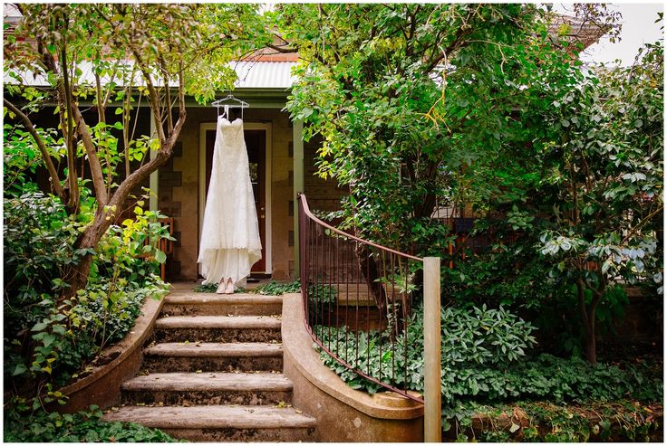 Stunning shot of the bridal gown on the Homestead steps. Photo by Barb & Mr Boord Photography.