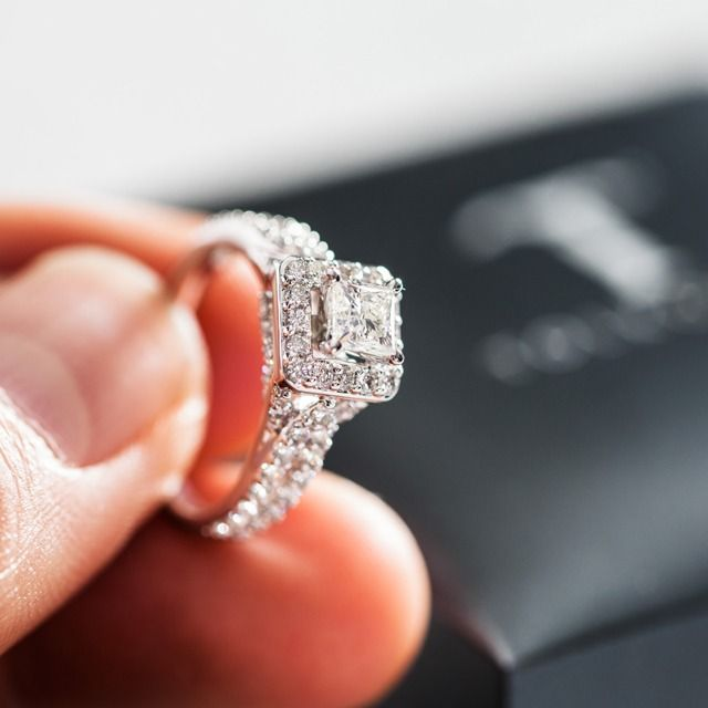 This Tolkowsky engagement ring has a diamond halo enhancing a gorgeous princess-cut center stone.