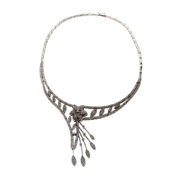 Garnityr i fyra delar med armband, örhängen, ring samt collier med dekor av blommor, infattade med briljantslipade diamanter. Armband, längd ca 19 cm. Stiftörhängen, ett par, höjd ca 50 mm. Ring, storlek 16,5. Colliér, längd ca 42 cm.
