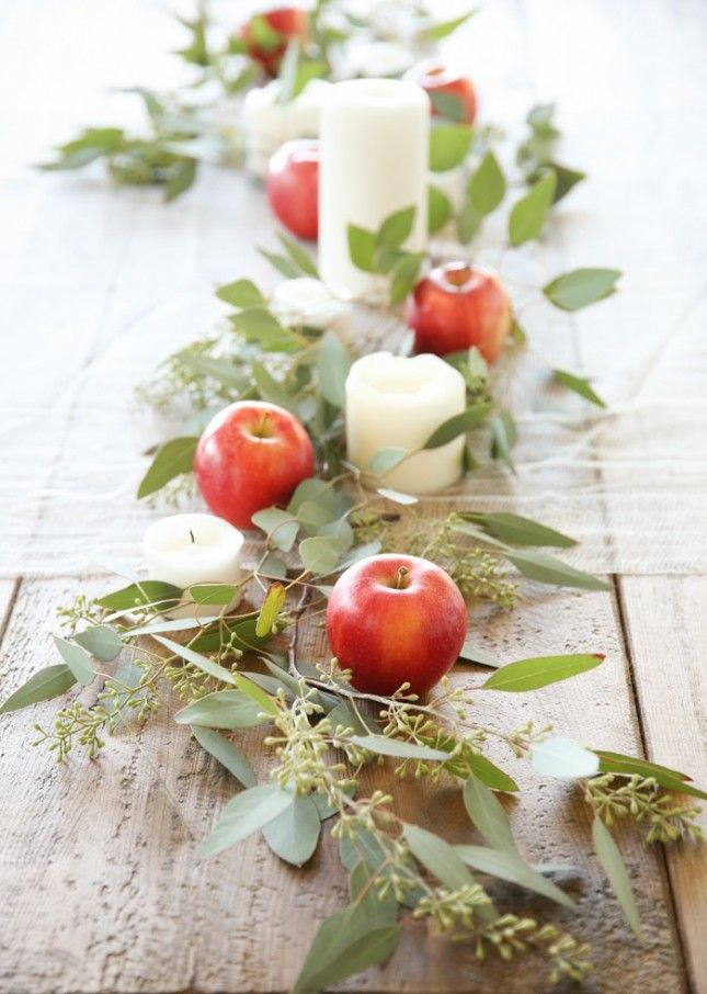 Use apples, fresh foliage + candles in place of a table runner.