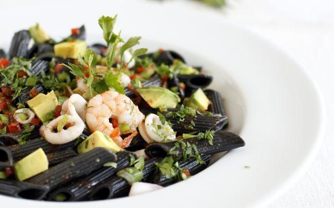 Ensalada fría de pasta de tinta de calamar con camarones, calamares y palta con dressing mediterráneo