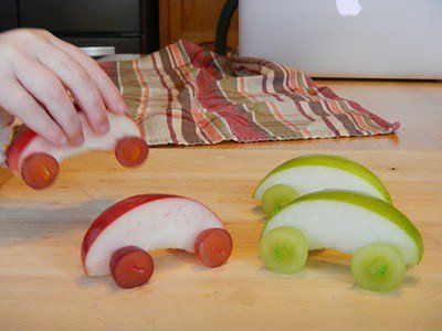 This is a good healthy snack for a kid. It is an apple with grapes as wheels.